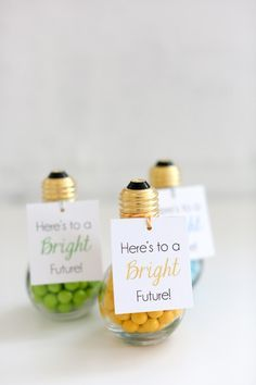 """DIY Graduation Party Favors: Thank your guests for attending the party with a cute, creative party favor. Say cheers to a bright future with colored chocolate candies packaged in a faux light bulb (available at party stores or online) and attaching our free """"Here's to a Bright Future!"""" printable favor tag."""