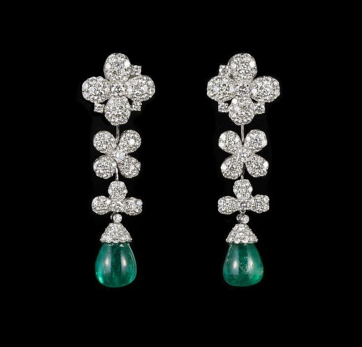 Adler, ensemble comprenant 1 collier et 1 paire de clips d'oreilles en or gris 750 à décor de trèfles serti de diamants taille brillant (total env. 59 ct) et retenant des émeraudes taille gouttes (total env. 132 ct).
