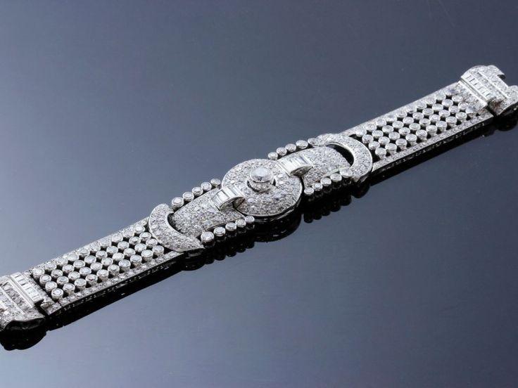 Elégant bracelet ruban en platine 850 millièmes, centré d'un motif géométrique orné d'un diamant taille ancienne en serti clos épaulé de diamants baguettes et ronds brillantés. Tour de bras articulé décoré… - Chevau-Legers Enchères - 13/12/2015