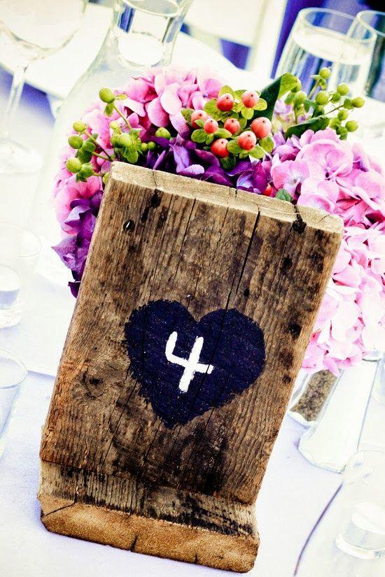 Originales ideas para numerar las mesas de una fiesta o evento con centros de mesas de madera.