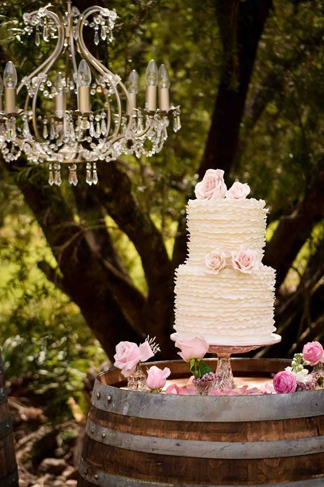 Wedding Cake display on top of wine barrel dotted with pink flowers.
