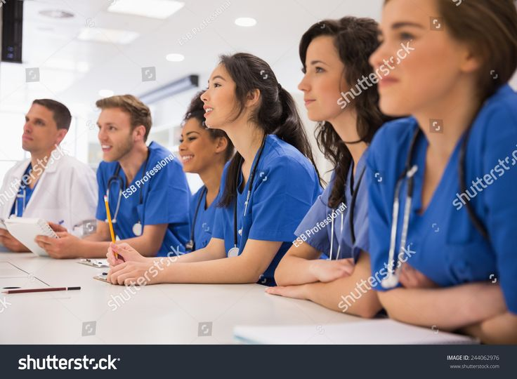 Medical students listening sitting at desk at the