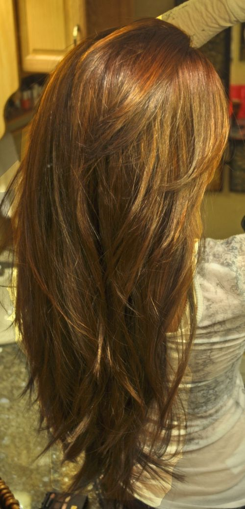 long layered haircut for thick hair cut in long distinct layers which curve naturally for an added textured effect and shape a shattered V-line at the ends. Warm honey highlights