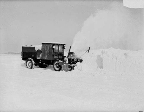 Image of a snow plow truck with a blower, clearing snow from a large, flat area in Chicago, Illinois.