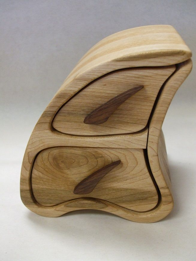 """Chris made this funky shaped maple jewelry box has oak handles and is lined with rayon flocking. It is finished with tung oil and protected with beeswax. The box measures 5 1/4"""" high by 4 5/8"""" wide at the bottom by 4"""" deep.  Email info@ucao.ca for availability."""