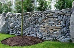 kreative Gartenmauer als Trockenmauer aus Flußsteinen