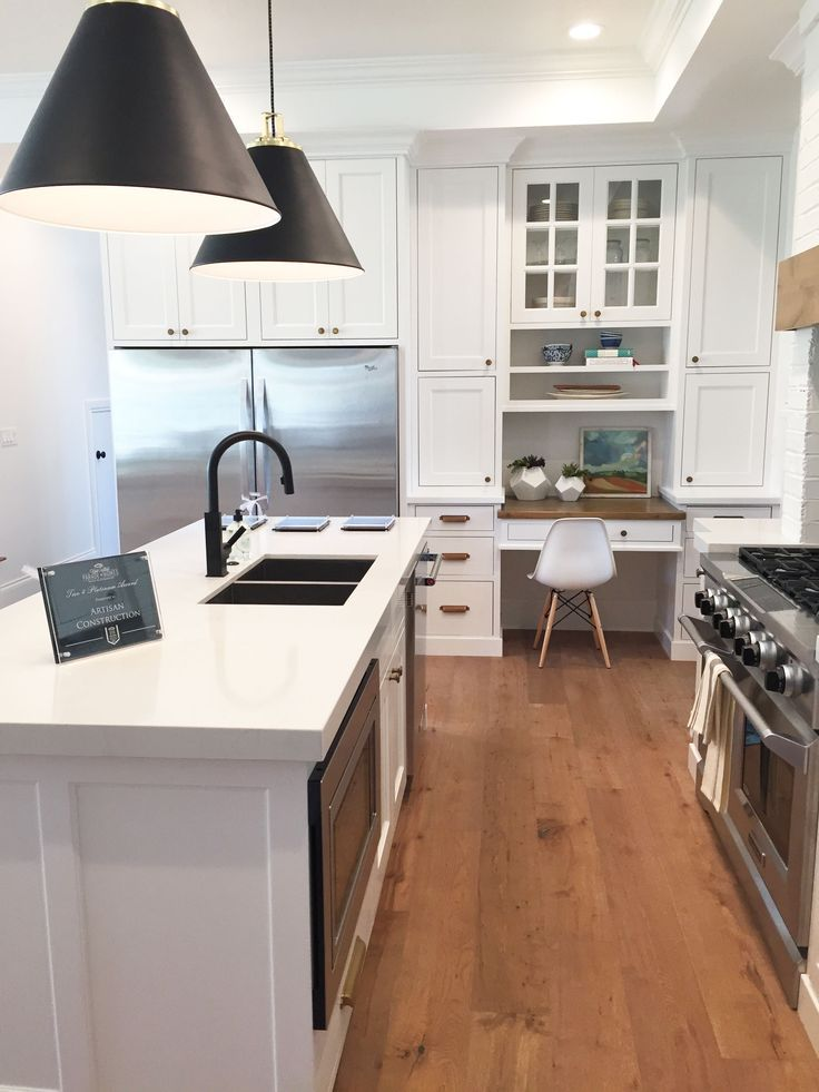 Narrow kitchen layout, double fridge, painted brick in kitchen, warm wood in kitchen, large kitchen island, white kitchen, desk in kitchen
