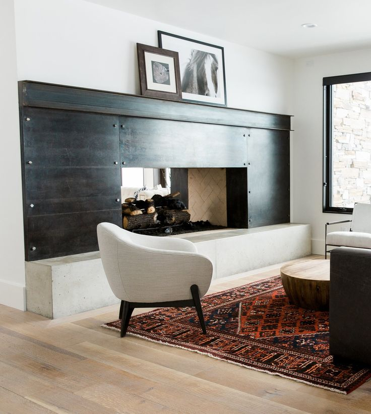 The fireplace surround is steel panels attached with rivets and the mantel is an actual I-beam. After it was installed, we did a black patina over the entire thing to give it a rustic, yet sleek look. The hearth is poured concrete.