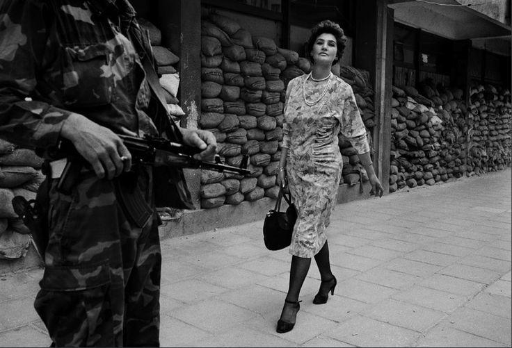 """Sarajevo, Bosnia, 1995 - Photograph of Meliha Varesanovic by Tom Stoddart """"This was her war. She looked so perfect with her head held high, immaculately made up, walking to her job in a government department. She was sending a message to the people surrounding her country, 'you will never win'. I went back to Sarajevo ... to find [her], and she agreed to me taking her photo in the exact same spot. She is still very beautiful and a very special person."""""""