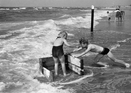 Twee kinderen spelen in de branding bij een strandpaal met de resten van een aangespoeld houten krat, 1960.
