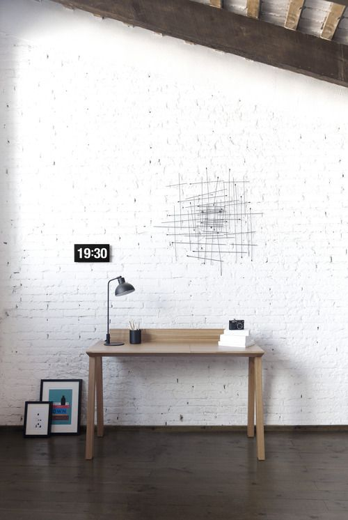 string art/clean lined table against rough white brick texture/black framed art/clock/lamp - all of it