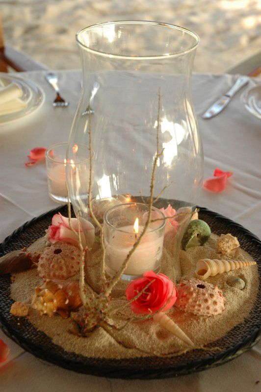 centerpieces, beach theme, hurricane lamp with sand and shells