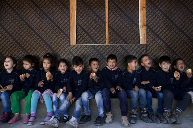 Syrian children refugees sit outside their classroom to eat their snacks at a non-formal school, built by NGO Kayany Foundation, where only Syrian students are enrolled, in the town of Saadnayel, in the Bekaa valley, Lebanon, Thursday, May 12, 2016. More than 400,000 Syrian children need schooling in Lebanon. Lebanese Education Minister Elias Bou Saab said Wednesday 100,000 Syrian children have been registered in public schools.