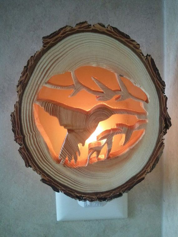 Hummingbird flickers at dusk. This night light is hand-made from Douglas fir wood using a scroll saw and an amber colored plastic sheet diffuser. No two night lights are the same as the natural rings