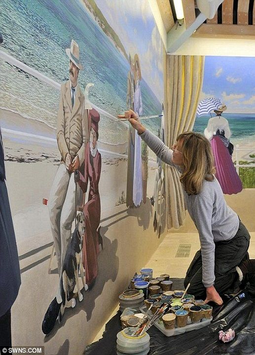Who needs a holiday: Janet Shearer paints a period beach scene on the wall beside a hotel swimming pool