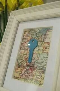 Key to 1st home with map of town behind it in frame