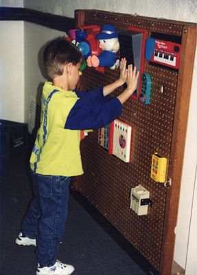 Create a sensory activity center for blind children. This activity center is made out of peg-board and decorated with toys varying in texture and ones that also play music.