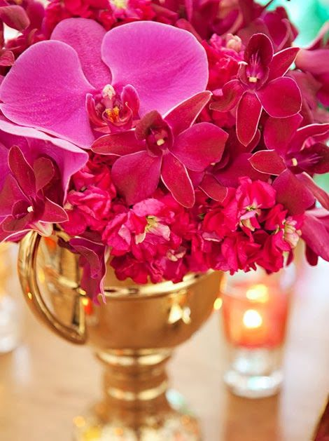 The reds and pinks of the flowers look really good against the gold vase!