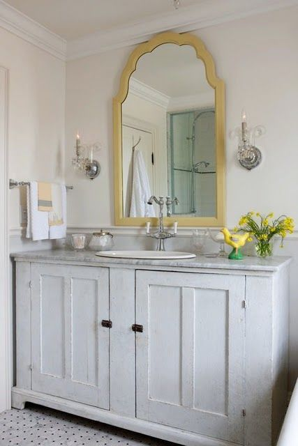 White and creme with a pop of yellow in the bathroom with a white and black floor and marble counter top.