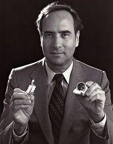 Theodore Harold Maiman, durante su trabajo en los Laboratorios de Investigación de Hughes como jefe de la sección en 1960. Desarrolló y patentó el primer láser, que usaba un rubí rosa bombeado por una lámpara de flash que producía un impulso de luz coherente, con el cual ganó un reconocimiento mundial.  En 1962 Maiman fundó su propia compañía, la Corporación Korad, consagrado a la investigación, desarrollo y fabricación de láseres.   Fue galardonado con el Premio Japón por su trabajo…