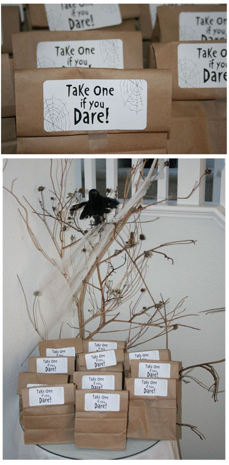 """Simple party favors were made using paper lunch sacs, white shipping labels, and a creepy spider web font. Placed atop a table near a """"haunted"""" tree."""