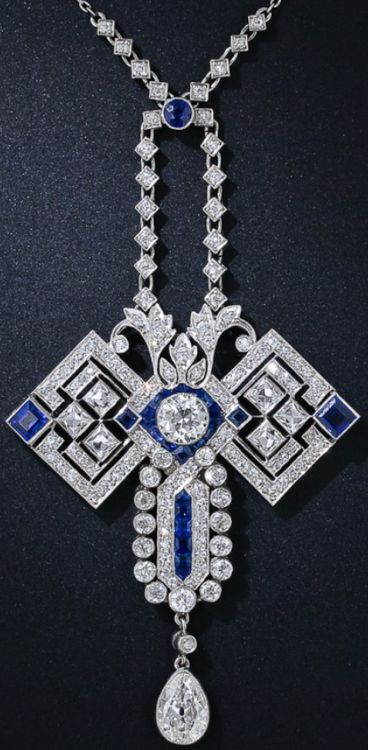 """Art Deco Diamond and Sapphire Butterfly Pendant Necklace, circa 1920s. The """"wings"""" are comprised of 6radiant and sizable French-cut diamonds and a pair of square sapphires. The head centers on a bright European-cut diamond framed in electric blue calibre sapphires, and the abdomen features a center row of calibre sapphires framed by diamonds. An old mine pear shape diamond dangles below. 4.50 carats total diamond weight. An applied plaque on the reverse  reads """"K.A.H - A.E.H. 1865-1915""""."""