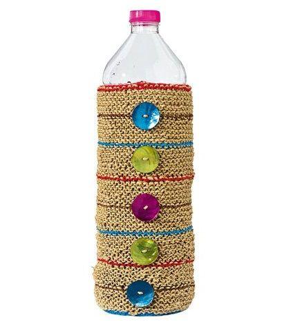 Bottiglie rivestite   Bottoni perline carta ritagli di tessuto juta Queste bottiglie sono realizzate tutte allo stesso modo. Una bottiglia di plastica ricoperta di biadesivo e decorata nei modi più fantasiosi. Allo stesso modo si può procedere con base i bottiglie di vetro. 1. Un canovaccio da cucina sopra il quale sono state ricamate a punterba le parole acqua di sorgente. 2. Su un fondo di plastica blu nuotano pesci rossi e gemme di vetro. 3. Stoffa a pois a formare il fondo e lettere…