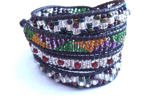 Fraaie wraparmband om vier keer om je arm te wikkelen, Chan Luu style. Donker paars leer, glaskralen wit, rood, en diverse kleuren rocailles. De armband sluit met een knoop en heeft een zilveren konijntje als bedeltje.