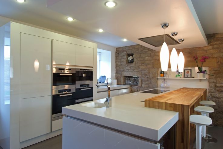 Make the most of the natural daylight in your kitchen with the use of high gloss reflective white units. Keeping the worktops white adds to the light airy feel. The central unit also features an induction hob and sink with a modern tap, showing that practical can still be beautiful in a contemporary kitchen.