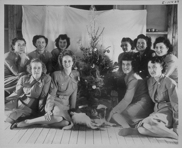 """Shown are WACs of the 2nd War Company, Norfolk Air Base, Barracks A, HRPE, seated around a Christmas tree with their mascot dog. Shown are: Pfc. Esther Olseen, Sgt. Natalie Smith, 1st Sgt. """"Bed-Check"""", T/5 Mary Smith, Pfc. Lois Laughlen, Pvt. Cory McGovern, Cpl. Ann Weathers, T/5 Ruth Ballard, Pfc. Mary Pfau, T/4 Mary Sofka and Cpl. Amy Bastiani ~"""