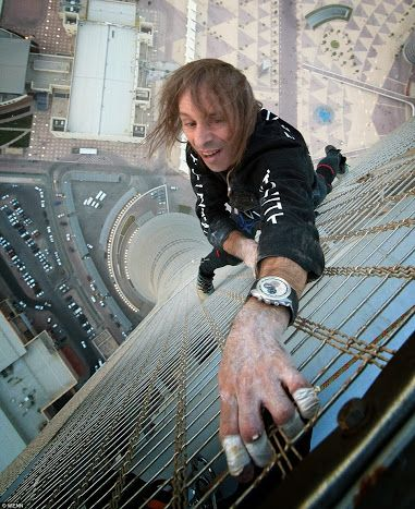 French climber Alain Robert known as Spiderman, climbs the last few floors of the largest building in the world in Dubai. 828 m or 2,715 feet.