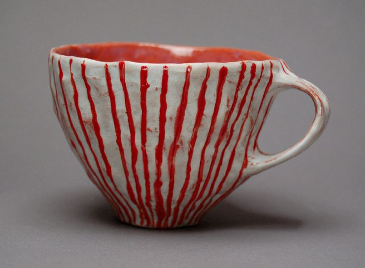 pinched cup with incised lines and red glaze.