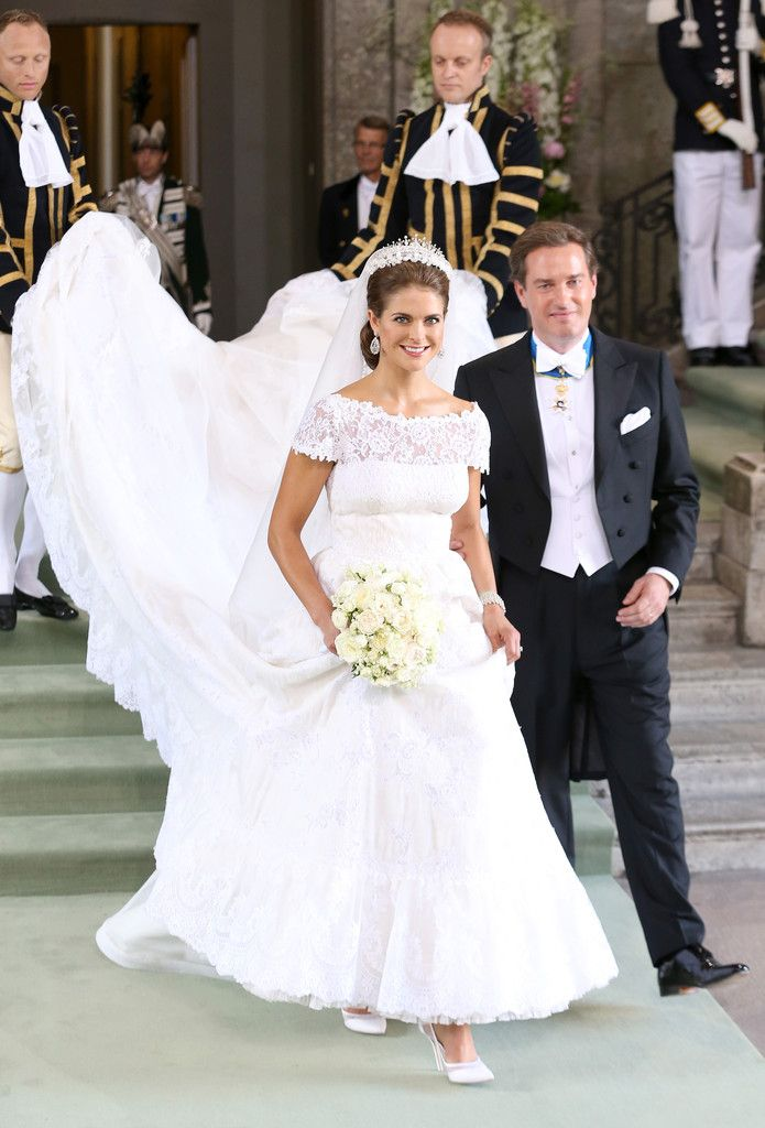 Princess Madeleine wedding dress a small vertical pleats at the waist opened into a full skirt with a flowing, four-metre train. The princess' six-metre long cathedral veil was also made from silk organdies, edged with tulle and embellished with Chantilly lace flowers.  Madeleine wore her hair swept back from her face in a simple yet elegant style.  The low bun was held in place by her royal tiara, which was decorated with a delicate garland of fresh orange blossoms.