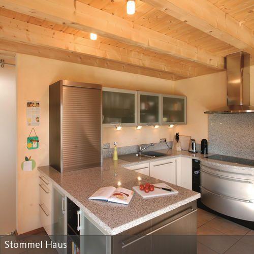 Dieser modernen Küche aus Edelstahl wird eine Deckenverkleidung aus Holz entgegengesetzt, um Gemütlichkeit zu erzeugen. Einzelne Lichtquellen hüllen den Raum…