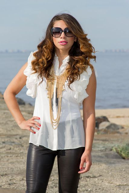 Bayann from Bay's Style Diary wearing leather pants and a white ruffle top with chunky gold necklace jewelry