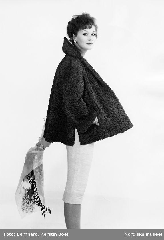 Modell i Persianpäls, vit kjol, örhängen och blombukett i handen. Foto: Kerstin Bernhard, 1958
