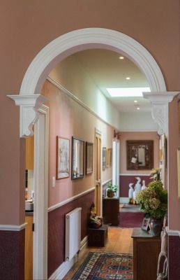 The wide hallway is welcoming with its peachy tones and arched entrance.