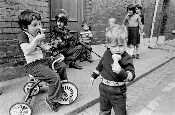 Children eat ice cream while soldiers patrol the streets, Londonberry, Northern Ireland, 1979  Peter Marlow