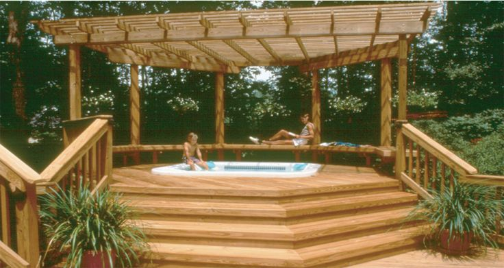 A deck built off of my lanai, with steps up to a sunken hot tub, underneath a pergola.