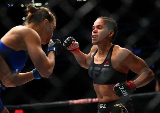Amanda Nunes moves in with a punch against Ronda Rousey during UFC 207 at T-Mobile Arena. - Mark J. Rebilas-USA TODAY Sports