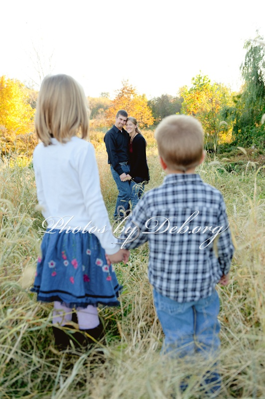 Different family photo. Shows sibling love and then making Mom and Dad in focus. Holding hands Autumn fall contemporary field country foxtails. http://myphotosbydeblife.blogspot.com/2012/12/autumn-is-my-favorite-time-for.html