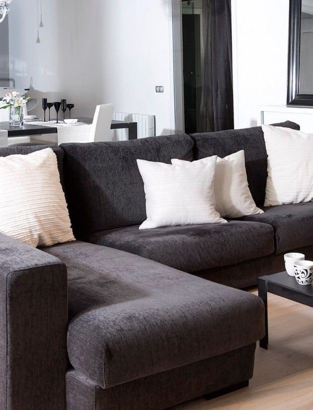 small loft apartment living room with black sectional sofa and white pillows interior design