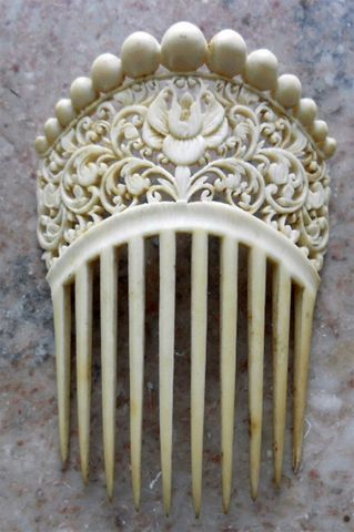 Chinese carved ivory comb made for export to the Victorian market (circa 1890). It has a lotus flower in the middle, with beautiful scroll work.