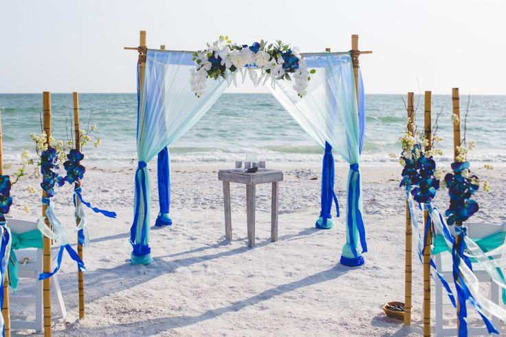 Royal, white and turquoise beach wedding arbor.