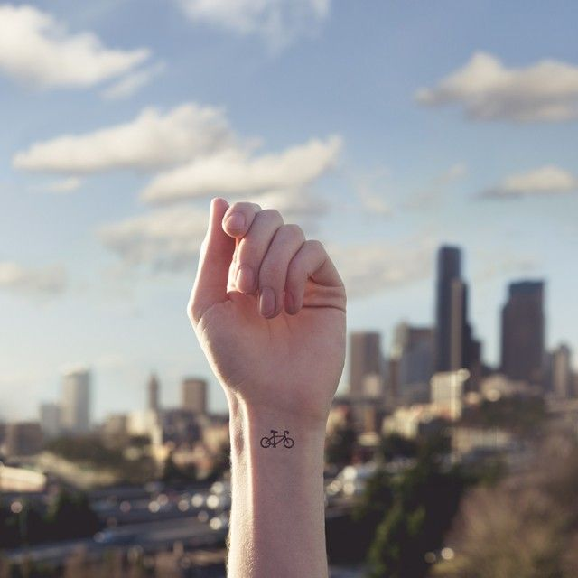 """American photographer Austin Tott did a series entitled """"Tiny Tattoos"""" which creates parallels between wrist tattoos and the background. A bike tattoo on a New York background, a letter tattoo on a mail background, quotes tattoo on books background ."""