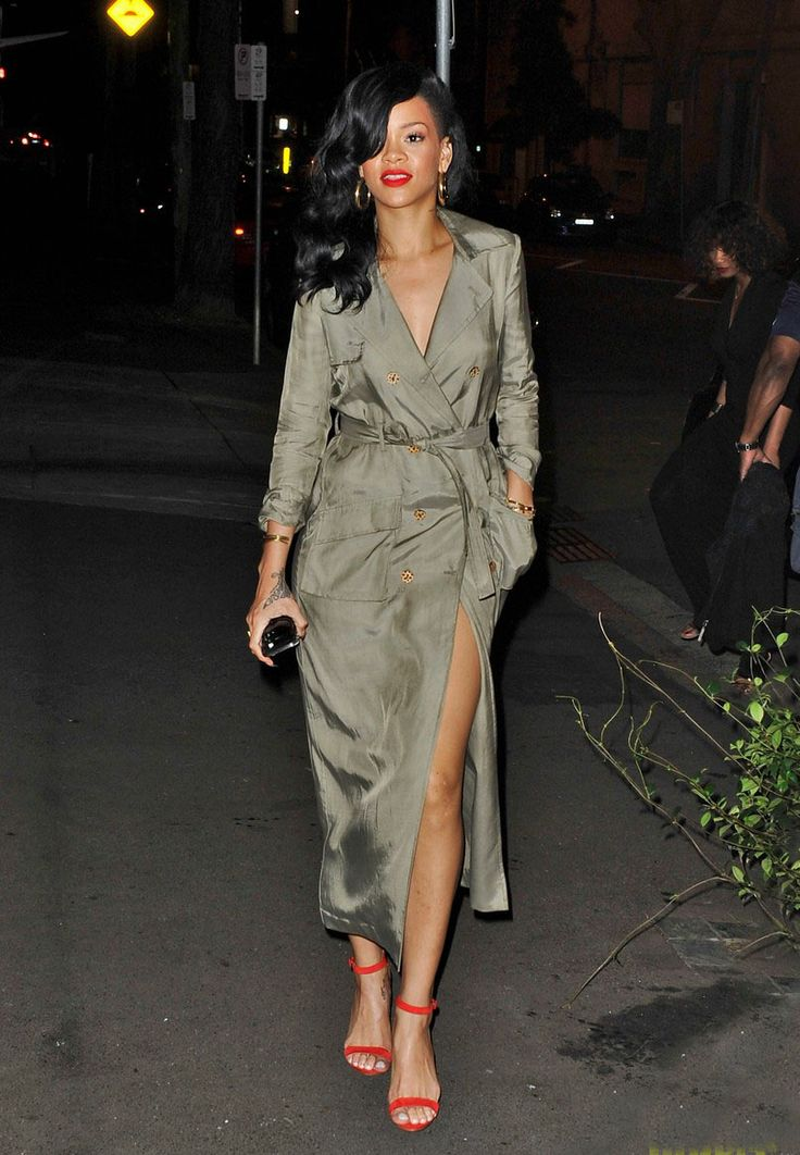 Rihanna in a military green trench coat with a high slit, colorful heels, & red lips.