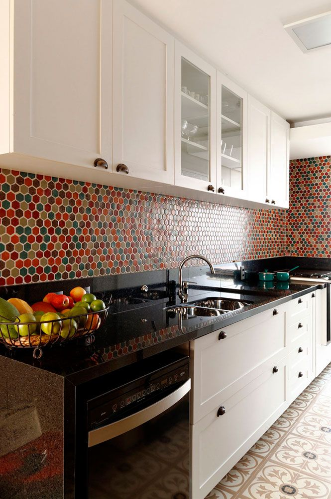 Red Kitchen Inspiration : Tiled backsplash brings pops of color into this modern kitchen : white bright cabinets : red gold orange terra cotta goldenrod turquoise tiles