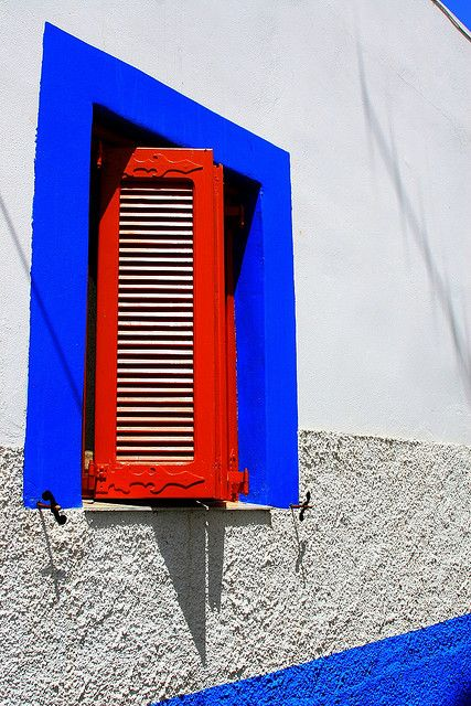 Facade with red wooden shutters and blue frame. Lipsi island, Dodecanese, Greece