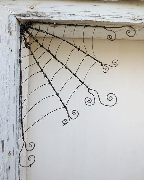 """Whether you have a quirky house or need a bit of a spooky Halloween theme, I think these wire spider webs are really cute.    Better still, they cost nothing but some time (both for locating some old wire and the """"weaving"""" itself).    Like it?"""