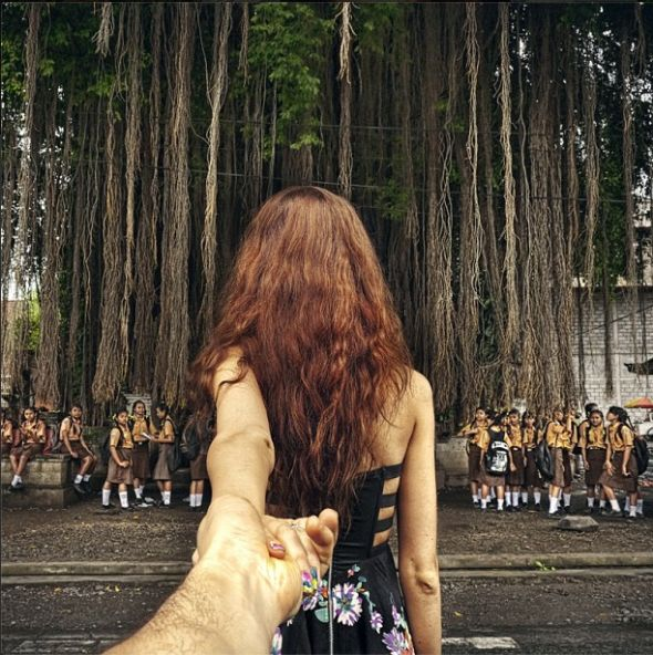 School girls pose under a large tree with hanging vines.